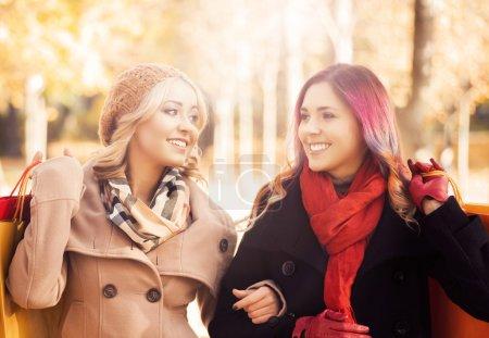 Photo pour Belles filles marchant dans le parc avec des sacs colorés. Journée ensoleillée d'automne. Réductions et concept de shopping . - image libre de droit