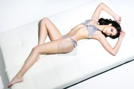 Photo pour Fit, sportive et sexy jeune femme en maillot de bain posant sur un canapé - image libre de droit