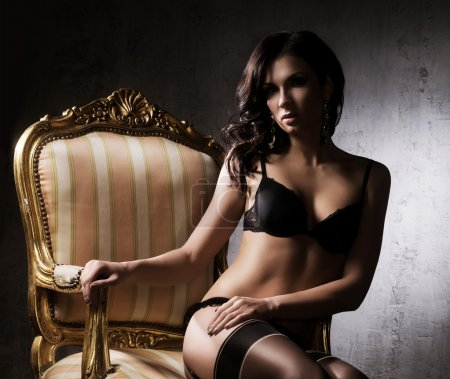 Sexy woman in underwear sitting in armchair