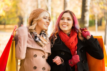 Two girls having a pleasant talk while walking the...