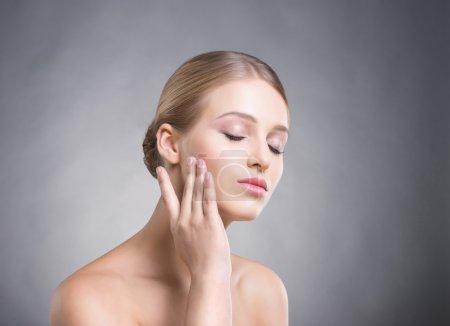 Photo pour Jolie fille de toucher sa peau lisse sur les joues sur fond gris. - image libre de droit