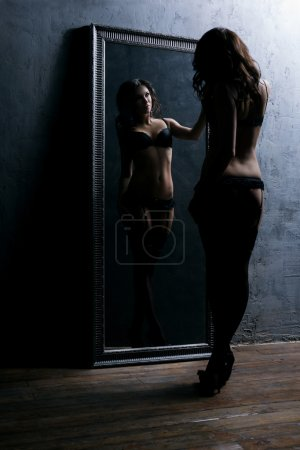 sexy woman posing and looking in the mirror
