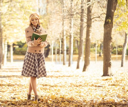 woman  in  autumn park with book.