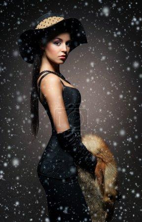 Photo pour Jolie jeune femme sur le fond rétro avec des flocons de neige . - image libre de droit