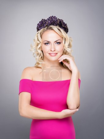 Photo for Portrait of gorgeous, young lady wearing pink dress and purple wreath over grey background. - Royalty Free Image