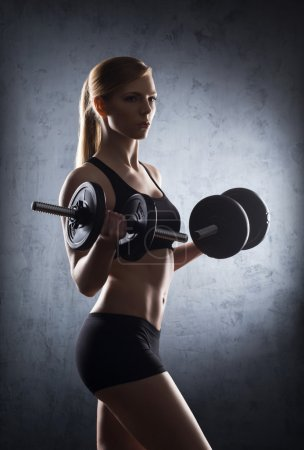 Young and fit woman with dumbbells