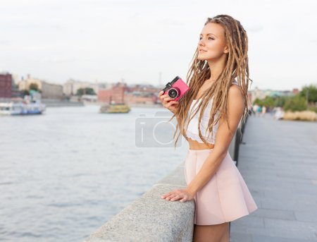 Portrait of Trendy Girl with Dreads and Vintage Camera Standing by the River. Modern Youth Lifestyle Concept.
