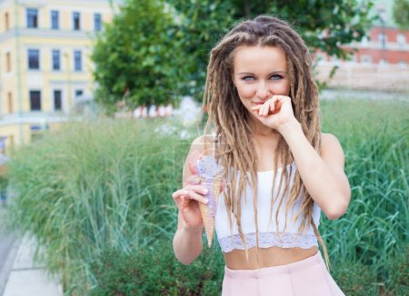 Young sexy blonde girl with dreads eating multicolored ice cream in waffle cones in summer evening,  joyful and cheerful.  European city center, at the park. Look at the camera