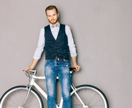 A young man with mustache and beard is near fashionable modern fixgear bicycle. Jeans and shirt, vest and the bow tie hipster style. Gray background. Toned color. Looking at the camera