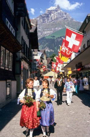 Photo for Engelberg, Switzerland - 2 May 2007: two young girls dressed in traditional costumes walk in the main street of Engelberg in the Swiss Alps - Royalty Free Image