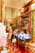 Zobrazeno textilu pro zákazníky v jejím obchodě prodavačka