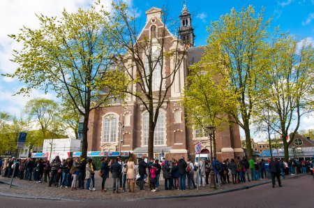 People stand in a queue to the Anne Frank House Museum in Amsterdam.