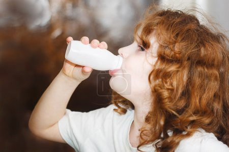 Little girl is drinking for milk or yogurt from bottles. Portrai