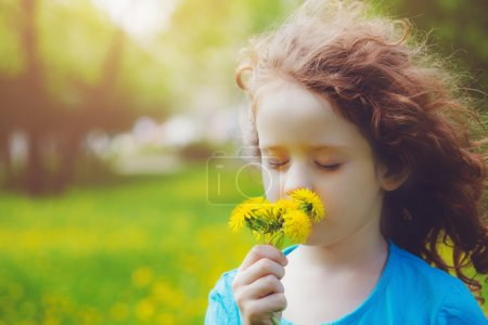 Cute little girl with yellow dandelions in the field. Background
