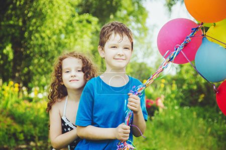 Happy children with balloons at summer park. Happy family concep