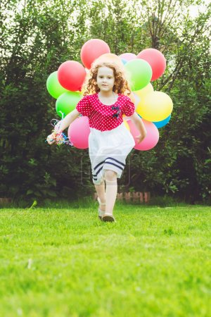 Little curly girl running with colored balloons. Happy childhood