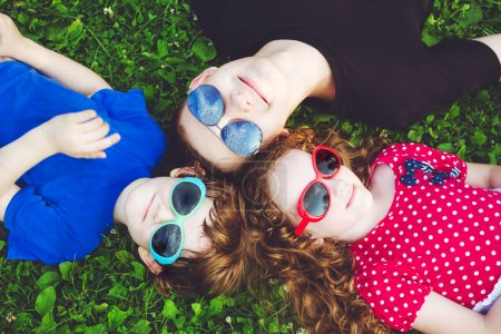 Happy children in glasses lying on the grass. Happy family conce