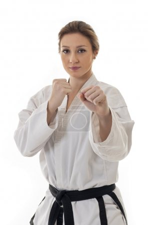Blonde martial arts girl in kimono exercising karate.