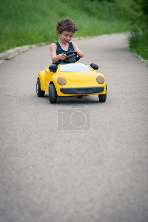 Young kid playing with toy car outdoors