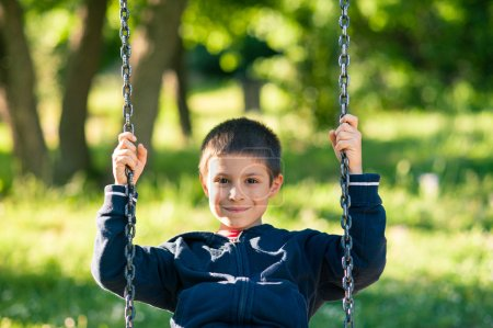 Young kid swinging on a sunny day with trees