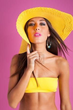 Beautiful smiling bikini girl against colorful pink background.