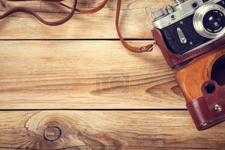 Old retro camera on wooden table background. Copy ...