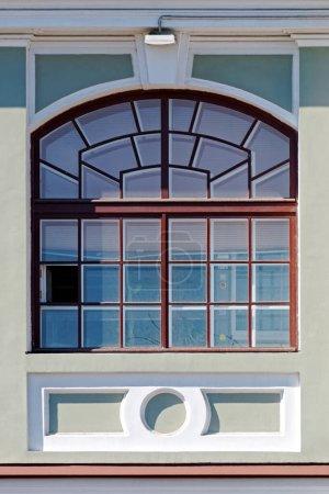 Fenêtre rectangulaire cintrée avec un cadre brun contre un mur gris. D'une série de fenêtres de Saint-Pétersbourg.