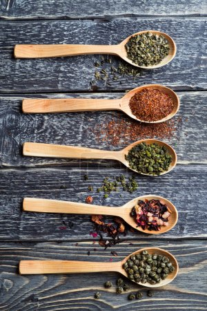 Photo for Composition with tea in wooden spoon on dark wooden background - Royalty Free Image
