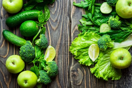 Photo for Fresh green vegetables and fruits on vintage wooden background. Detox, diet or healthy food concept - Royalty Free Image