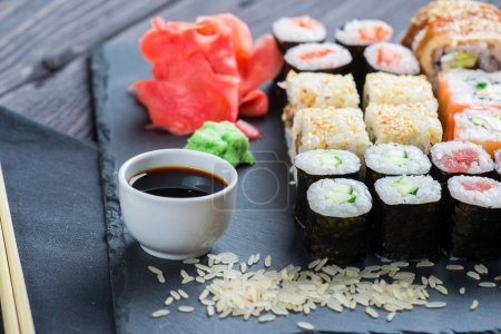 Photo pour Différents types de sushis servis sur pierre noire - image libre de droit