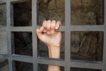 Photo for Close up of hand of a prisoner grabbed the bars of the prison - Royalty Free Image