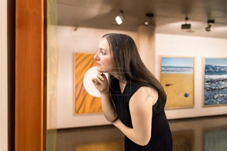 Photo for Woman closely scrutinizing a painting at an exhibition of the museum.Background photos are my property - Royalty Free Image