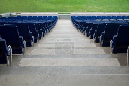 Photo pour Étapes numérotées dans un stade situé entre les sièges en plastique bleu - image libre de droit