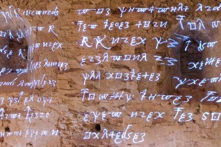 Leuchtende antike Runen Schriftzeichen und Buchstaben aus feurigen Texten antiker Schriften auf rauer Steinmauer