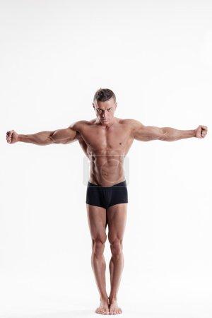 Photo pour Jeune bodybuilder musculaire posant sur fond blanc . - image libre de droit