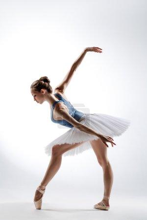 Photo pour Belle danseuse de ballet posant sur un fond de studio - image libre de droit