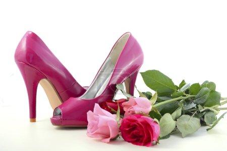 Photo pour Chaussures à talons hauts rose féminin avec des roses sur la table en bois blanc pour la journée internationale de la Womens, 8 mars. - image libre de droit