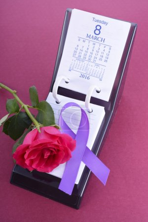 Photo pour Calendrier de bureau pour le 8 mars, Journée internationale de la Womens, avec bouton de rose et symbole du ruban violet, sur fond rose. - image libre de droit