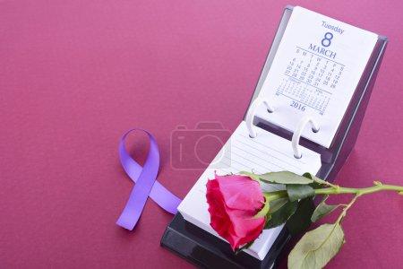 Photo pour Calendrier de bureau pour le 8 mars, Journée internationale de la Womens, avec bouton de rose et symbole du ruban violet, sur fond rose, avec un espace copie - image libre de droit