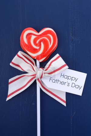 Photo pour Happy Fathers Day red and white lollipop gift on dark blue wood background. - image libre de droit