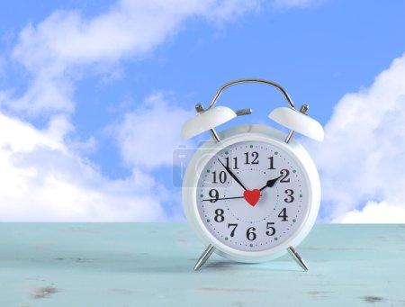 Photo pour Heure d'été horloge blanche sur une table en bois bleu aqua vintage contre un ciel avec fond nuageux . - image libre de droit