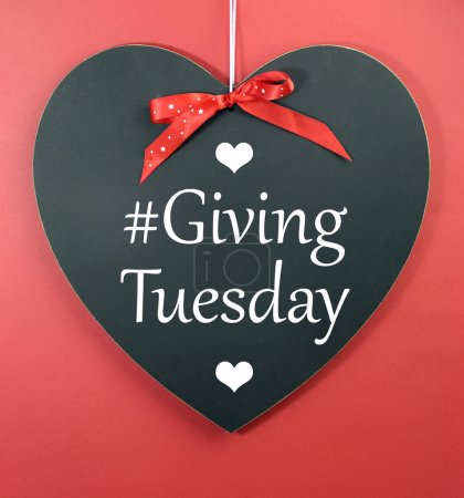 Photo for Giving Tuesday message greeting on black heart shape blackboard against a red background. - Royalty Free Image