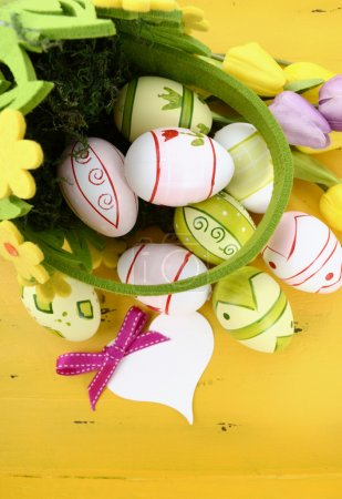 Photo for Happy Easter green and yellow felt basket of of pink, white and green easter eggs on rustic vintage yellow wood table, with heart shape greeting card, vertical. - Royalty Free Image