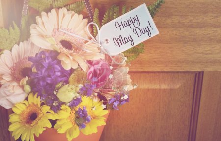 Photo pour Happy May Day traditional gift of Spring flowers in orange cone hanging from door handle on wooden door, with applied retro vintage style filters and added sun lens flare. - image libre de droit