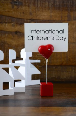 Photo pour International Childrens Day concept with paper dolls on dark wood background, with message on red heart sign. - image libre de droit