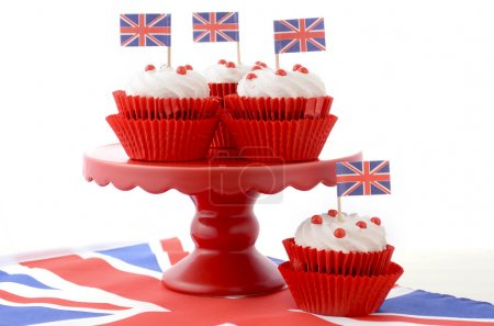 Photo pour Red white and blue theme cupcakes on red cake stand with UK Union Jack flags on white wood table for Queens Birthday and Great Britain party food. - image libre de droit