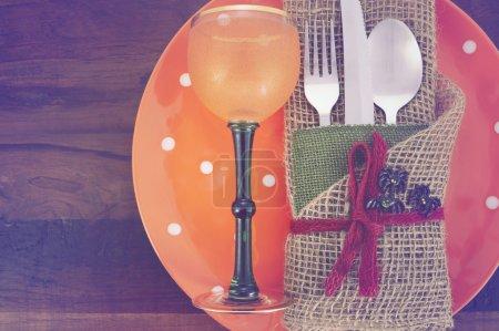 Photo pour Cadre rustique de table d'Halloween avec couverts enveloppés de toile de jute et assiette orange et gobelet de vin sur table en bois sombre avec filtres vintage rétro appliqués . . - image libre de droit