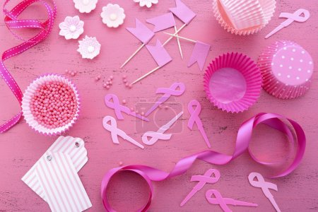 Photo pour Organiser un événement pour la journée du ruban rose, collecte de fonds de sensibilisation aux bonbons au sein, avec des décorations de cupcakes sur une table en bois rose vintage . - image libre de droit