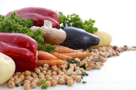 Photo pour Nourriture végétarienne comprenant des légumes, des noix et des légumineuses avec l'espace de copie sur le fond blanc. - image libre de droit