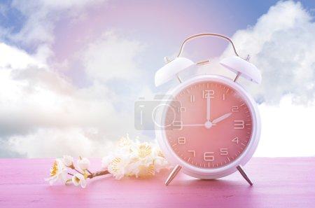 Photo pour Concept d'heure d'été printanier avec horloge rose sur table en bois rose avec fond bleu ciel, et filtres et fusée éclairante ajoutés . - image libre de droit